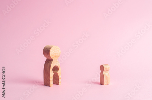 A wooden figure of a woman and a child stands near the magnifying glass Canvas Print