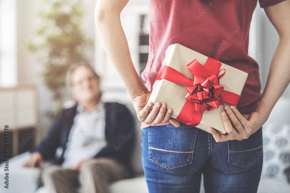 Fototapeta Young daughter gives her father a gift