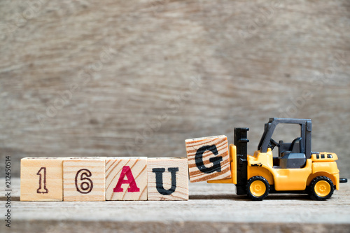 Vászonkép  Toy forklift hold block G to complete word 16 aug on wood background (Concept fo