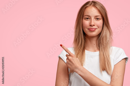 Fotografia  Studio shot of beautiful blonde female with satisfied expression, points with fo