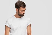Concentrated Handsome Young Male Focused Down, Has Dark Stubble And Hair, Wears Casual White T Shirt, Isolated Over Studio Background With Copy Space For Your Advetisement Or Promotional Text