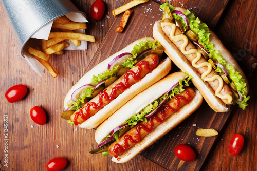 Fotografía Hot dog with grilled sausage, ketchup, mustard and fries on wooden kitchen board top view