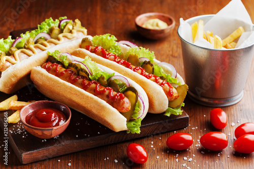 Hot dog with grilled sausage, ketchup, mustard and fries on wooden kitchen board. Traditional american fast food.