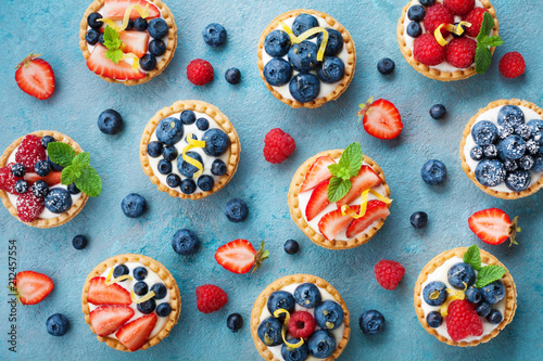 Photo Stands Dessert Colorful berry tartlets or cake for kitchen pattern. Pastry dessert from above.