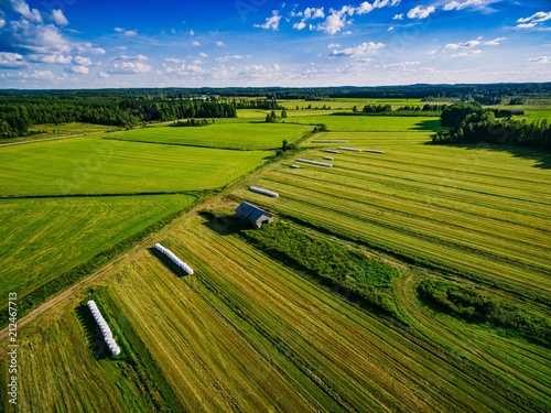 Fotografie, Obraz  Aerial view of green field harvest with old wood barn and bales of hay in white plastic in rural Finland