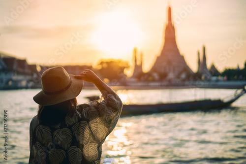 Poster Bangkok Young woman traveler traveling into Wat Arun Ratchawararam Ratchawaramahawihan Temple in bangkok, Thailand at sunset