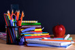 School supplies on blackboard background with copy space.