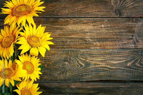 In de dag Zonnebloem Beautiful sunflowers on a wooden table. View from above. Background with copy space.
