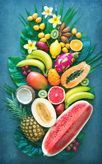 Fototapeta Owoce Assortment of tropical fruits with palm leaves and exotic flowers