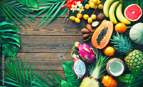 Photo Stands Fruits Assortment of tropical fruits with leaves of palm trees and exotic plants on dark wooden background