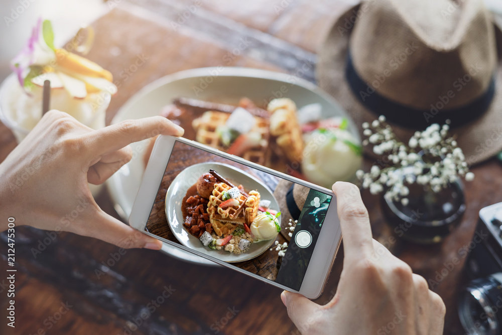 Fototapety, obrazy: Young woman taking photo of food with smart phone in restaurant