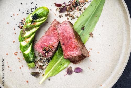 Photo Stands Ready meals Modern gegrilltes dry aged Filet Steak aufgeschnitten mit Bärlauch und Baby Zucchini als Draufsicht auf einem Teller mit scharfen Gewürzen