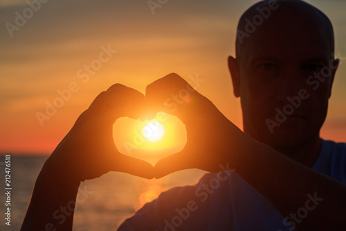 Garden Poster Coral men's hands in the form of heart against sunlight in sunset sky, twilight time. Hands in shape of love heart, Love concept.