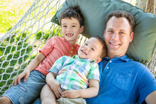 Caucasian Father Relaxing In Hammock With Mixed Race Chinese Sons