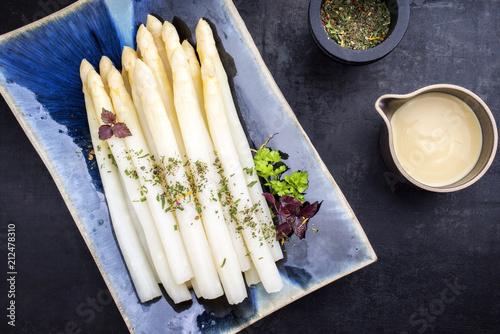 Traditioneller gekochter weißer Spargel mit Sauce Hollandaise als Draufsicht auf einem blauen Teller