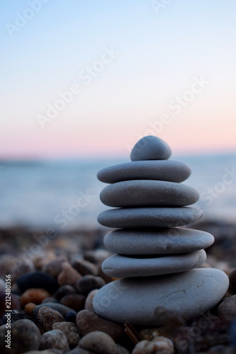 Photo Stands Zen A pile of flat stones on the beach. The sea and sunset in the background