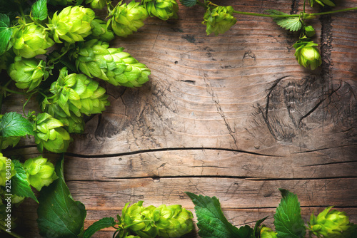 Fotomural Hop twig over old wooden cracked table  background