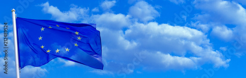 Flag of the European Union waving in the wind on flagpole against the sky with clouds on sunny day, banner, close-up