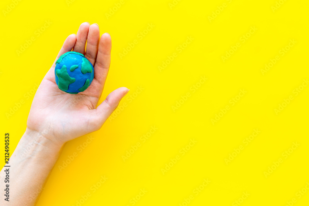 Fototapety, obrazy: Earth. Hand hold plastiline symbol of planet Earth globe on yellow background top view space for text