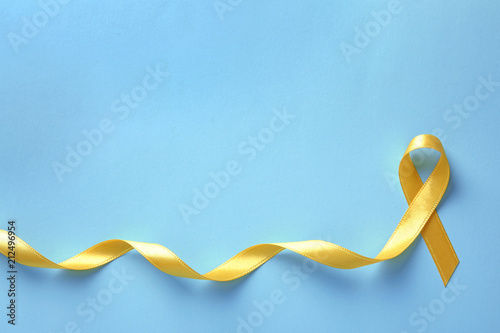 Fotografía  Yellow ribbon on color background, top view. Cancer awareness