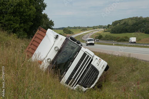 Photo The large truck lies in a side ditch after the road accident