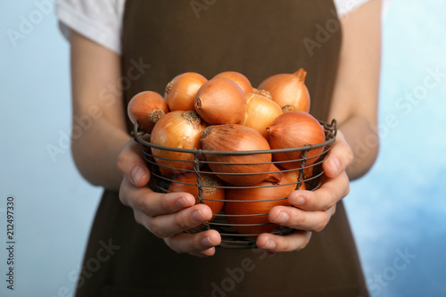 Woman holding basket with ripe onions on color background
