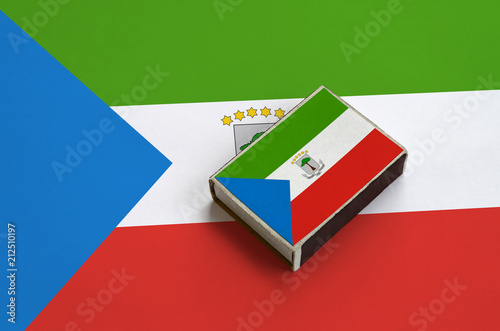 Fotografía  Equatorial Guinea flag  is pictured on a matchbox that lies on a large flag