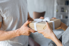 Partial View Of Man Presenting Wrapped Gift To Girlfriend At Home