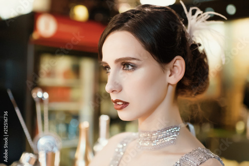 Fotografia  Close-up portrait of a young attractive woman in a 1920s style at the bar