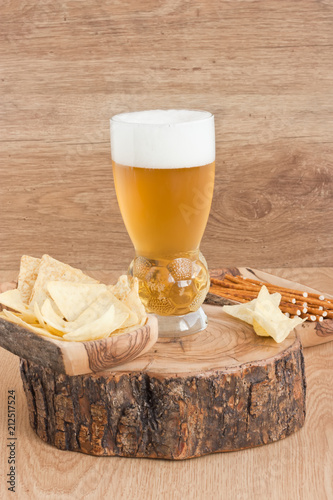 Foto op Aluminium Bier / Cider Glass light golden beer / Glass cold light golden beer with corn chips and salted straw on wooden background