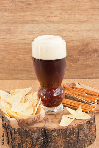 Foto op Aluminium Bier / Cider Glass dark beer / Glass cold dark beer with corn chips and salted straw on wooden background