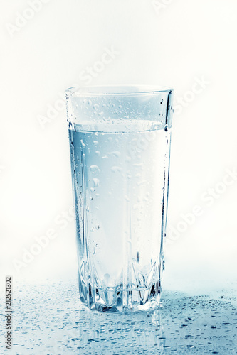 Papiers peints Eau Glass of cold water with drops and reflection, toned. Drink of health freshness aqua