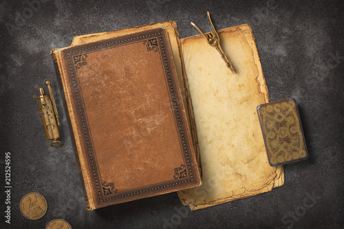 Fototapeta Steampunk / Gaslight themed mockup with a vintage book, a stack of grungy paper and antique brass items on a dark metal background obraz