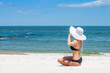 Beautiful woman in bikini and hat sitting on the beach enjoying summer holidays