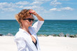 Beautiful happy woman in white shirt looking at the sea on beach.