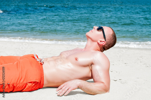 Fotografie, Obraz  Muscular young athletic sexy man lying on the beach