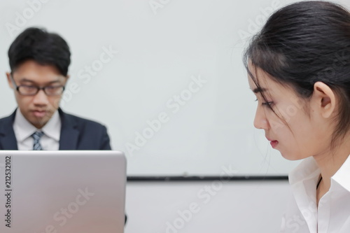 Close up face of unhappy Asian business woman having conflict with her colleague in office.