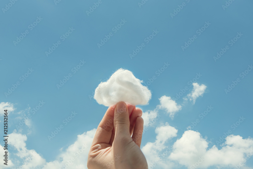 Fototapety, obrazy: Woman hand holding cotton wool on cloud sky background. The development of the imagination, copy space.