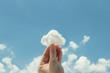 Leinwandbild Motiv Woman hand holding cotton wool on cloud sky background. The development of the imagination, copy space.