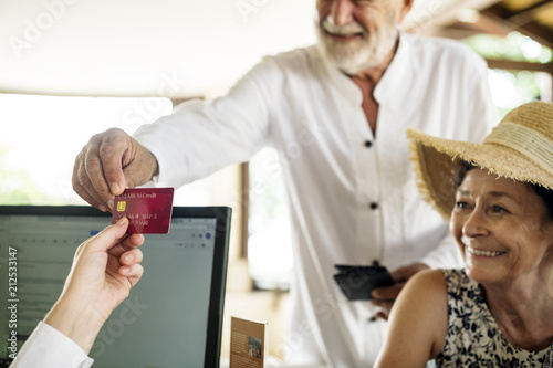 Fotografia  Old man giving credit card to receptionist
