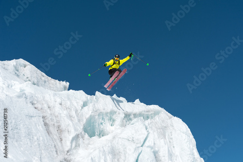 Poster Glisse hiver A jumping skier jumping from a glacier against a blue sky high in the mountains. Professional skiing