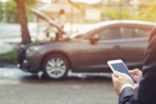 Close Up Businessman Hand Using A Mobile Smart Phone Call A Car Mechanic Ask For Help Assistance Because Car Broken Roadside. People Journey Friends Standing Wait Beside Broken Car Background.