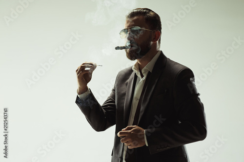 Fototapeta The barded man in a suit holding cigar
