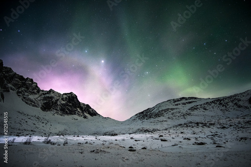 Aurore polaire Aurora borealis with sunrise shining over mountain range in the night sky