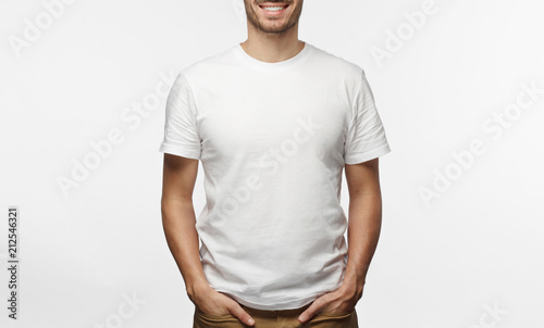 Fotografía Handsome man in white tshirt isolated on grey background, smiling, standing in h