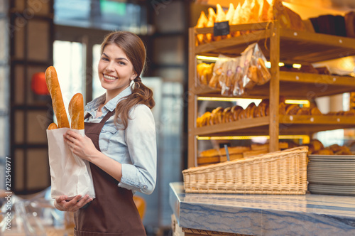 Poster de jardin Boulangerie Young smiling girl with baguettes