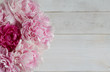 Bouquet of peonies on a white wooden background with copy space