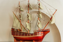 Model Of An Old Sailing Ship On White Wall Background.