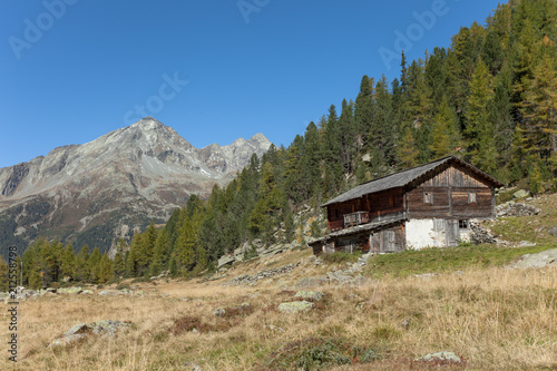 In de dag Alpen A closed cowshed at fall in front of a mountain meadow