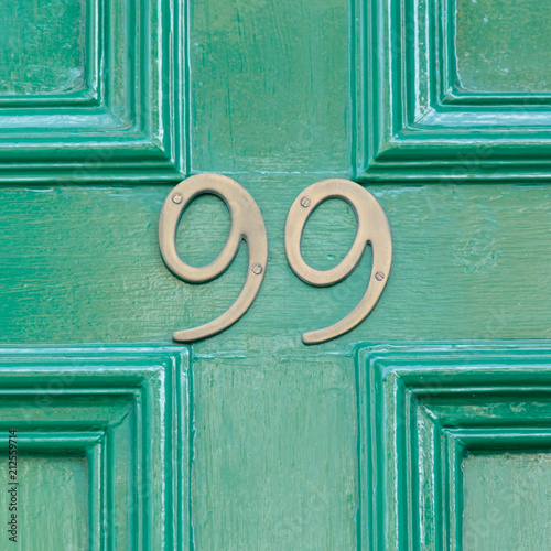 Photographie  Brass house number 99 sign on green painted door
